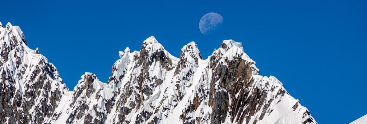 A mountain ridge with the Moon peeking out behind it